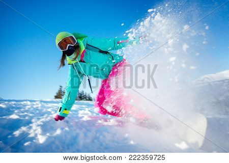 Snowboarder on snowboard rides through snow, explosion. Freeride snowboarding in Sheregesh Ski Resort