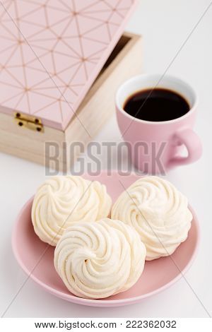 Homemade apple zephyr or marshmallow in pink plate with cup of coffee on white table. Valentine's or Mothers Day concept