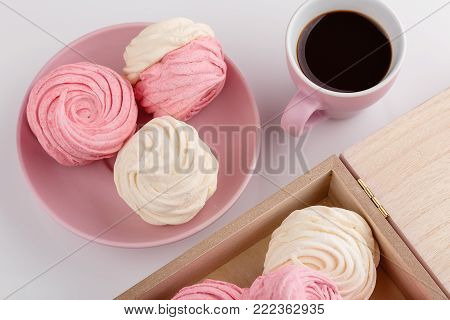 Top view of homemade zephyr or marshmallow in pink plate with cup of coffee on white table. Marshmallow, Meringue, Zephyr. Valentine's or Mothers Day concept
