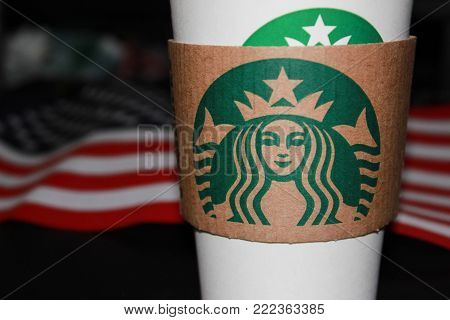 MOSCOW, RUSSIA - JANUARY 11, 2018: Starbucks Coffee White Paper Cup on American Flag Background at Black Table. Starbucks Corporation is an American Coffee Shop Company Founded in Seattle in 1971.