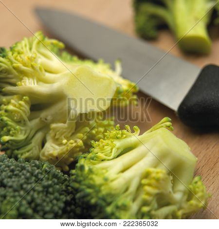 BROCCOLI FLORETS AND KITCHEN KNIFE ON WOODEN TABLE IN CLOSE UP