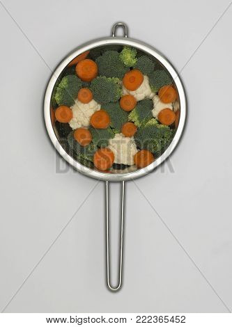 STAINLESS STEEL COLANDER CONTAINING FRESH CAULIFLOWER CARROTS AND BROCCOLI FLORETS