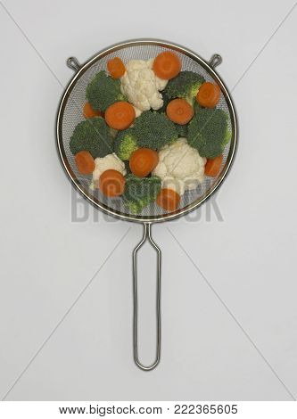 STAINLESS STEEL SIEVE CONTAINING FRESH CAULIFLOWER CARROTS AND BROCCOLI FLORETS