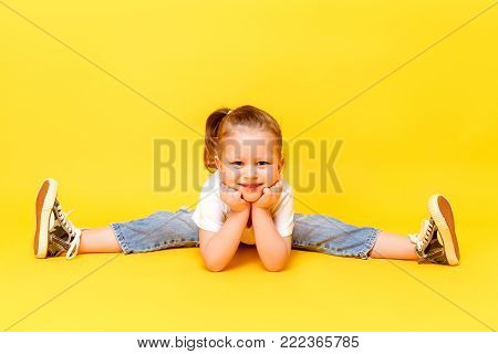 Adorable stylish girl posing on yellow color background