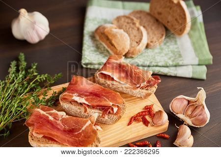 Sandwiches made from hand-made rye bread and thin chopped fresh bacon. Succulend bacon on a wooden board. Fresh green thyme and hot red pepper.