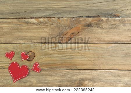 Red paper hearts on a wooden background. Valentine's Day. Copy space. Top view