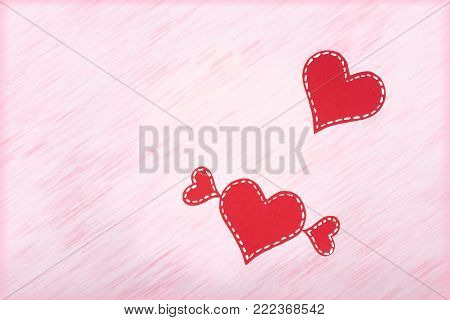 Red paper hearts on pink background. Valentine's Day. Copy space. Top view