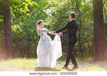 Young Beautiful Groom In Dark Blue Suit And Bride In White Crop Top Dress And Holding Big Wedding Bo