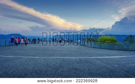 Sydney, Australia - Apr 18, 2017: Tourists congregate on the observation deck at Echo Point to enjoy the setting sun. This wilderness area forms part of the Blue Mountains National Park. Image features escarpment and Jamison Valley.