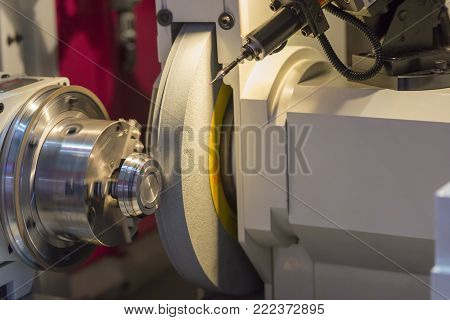 The cylindrical grinding machine with the steel part .Hi precision manufacturing concept.