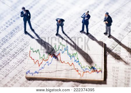Businessmen are skeptical looking at stock market charts.