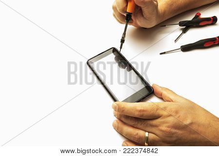 Man using precision screwdrivers on his smartphone in a close up view of his hands in a concept of screen replacement, repairs and maintenance over white with copy space
