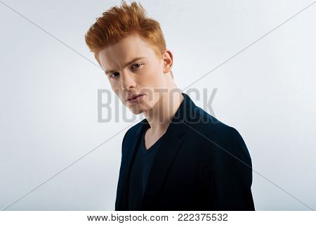 Determination. Attractive unsmiling red-haired young man wearing a jacket and staring and having a stylish haircut