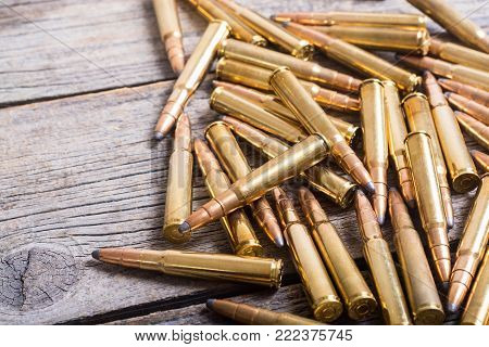 Bullets . Gun cartridge 8mm caliber on wooden background poster