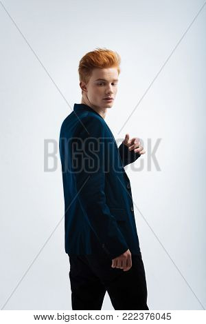 Seriousness. Handsome thoughtful young red-headed man wearing a jacket and having a serious expression on his face and looking over his shoulder