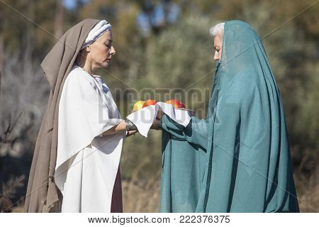Alcuescar, Spain - December 17th, 2017: Reenactment of Iberian Goddess Ataecina ritual. Priestess receiving offering from devotee. Performed by Lusitania Romana Group