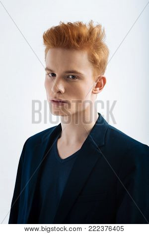 Stern look. Good-looking unsmiling red-haired young man wearing a jacket and staring and having a modern haircut