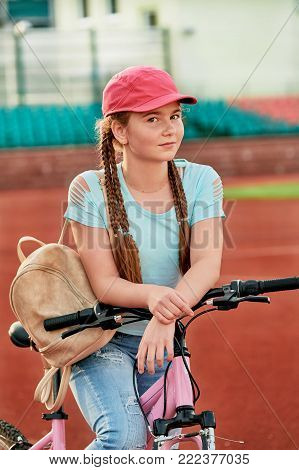 Teenage girl relaxing on a stadium.Girl relaxing on a bike free time. Portrait of a teenage girl in a pink color cap looks at the camera.