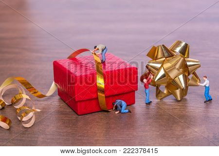Creative concept with miniature people and a gift box on a wooden background. The process of packing gifts. Gold ribbon, bow, festive beads. Creative concept of teamwork.
