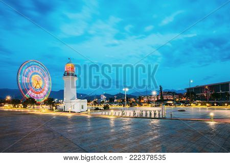 Batumi, Adjara, Georgia. Ferris Wheel In Motion And Pitsunda Lighthouse At Promenade In Miracle Park, Amusement City Park On Blue Evening Sky And Hilly Background. Blue Hour. Evening Or Night Time