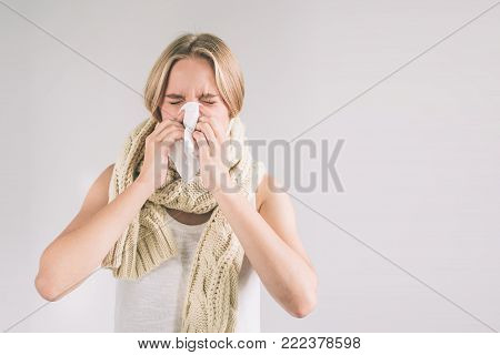 studio picture from a young woman with handkerchief. Sick girl isolated has runny nose. Female model makes a cure for the common cold