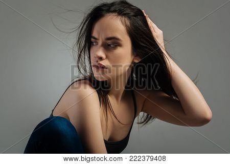 Seriousness. Pretty earnest long-haired young woman sitting and looking over her shoulder and touching her hair