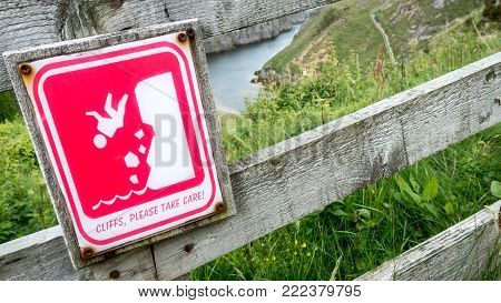 Smoo Cave cliffs, Scotland; safety warning sign. An illustrated sign on a fence above Smoo Cave, Durness, Scotland, warning of the dangers of the environment. The drop is visible through the fence.