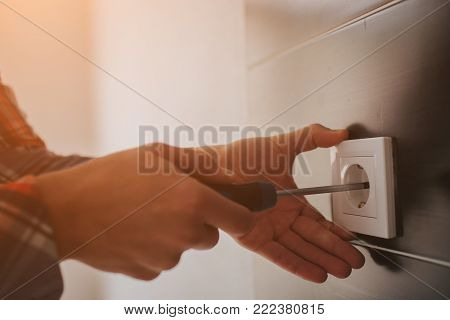 Electrician, Electrician installing new current socket with screwdriver. Installing electrical outlet or socket - closeup on electrician hands. poster