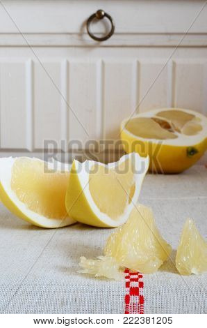 Piecs of pamela fruit on a white background in rustic style
