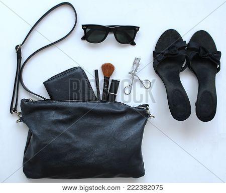 Open female black bag and feminine objects