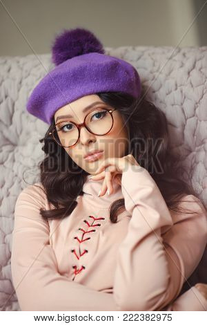 Beautiful young asian woman indoors. Portrait of attractive girl sitting on sofa at home. Elegant lady wearing glasses trendy dress and cute hat looking at camera. Beauty fashion shot of gorgeous slim model.