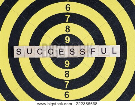 Word spell Successfull by wooden box font on dart board (Business concept)