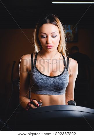 Closeup, Happy woman using an elliptic trainer in a fitness, She smiling while exercise in morning. sunlight effect.