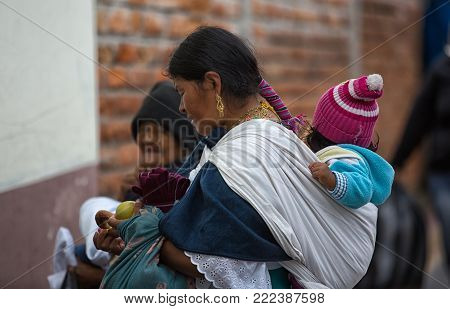 Otavalo, Ecuador - December 30, 2017: indigenous quechua woman carrying child on her back  in the local market