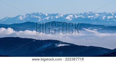 panorama of High Tatras mountains range from Lysa hora hill in Moravskoslezske Beskydy mountains during winter day with clear sky