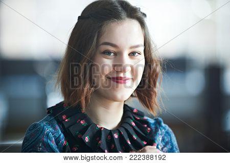 Young cheerful woman studio headshot portrait indoors