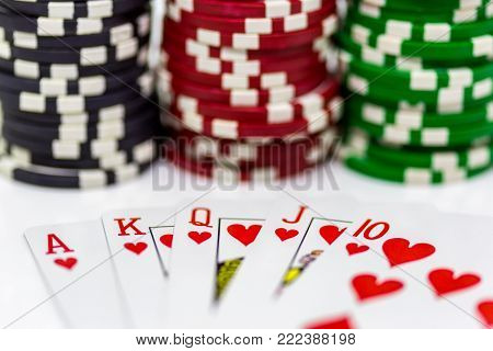 A royal flush with blurred poker chips in the background on a white background