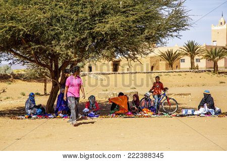 Tinzouline, Morocco - February 26, 2016: Berber Vendors Sit In The Shade Of A Spreading Tree In A Mo