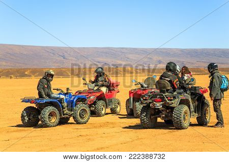 Merzouga, Morocco - February 21, 2016: Several Riders Wait With Their Quad Atvs In The Sahara Desert
