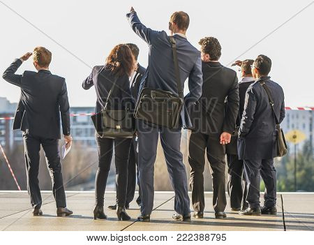 La defense, France - March 6, 2014: A group of business people in suits stand on a concrete platform fronted by caution tape in La Defense, France. They shade their eyes as one man points into the distance. Several buildings can be seen in the background