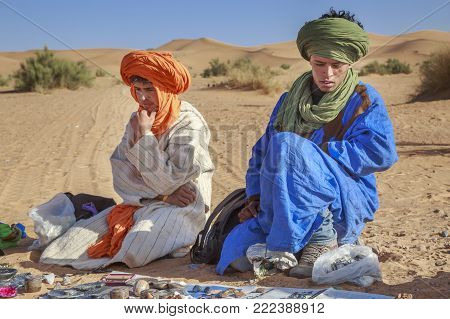 Merzouga, Morocco - February 25, 2016: Nomad souvenir vendors of the Sahara desert dressed in colorful robes and turbans, sitting on the sand under a bright blue sky with their wares spread out on blankets in front of them.