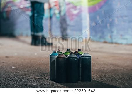 low section of street artist painting graffiti at night, cans with aerosol paint on foreground