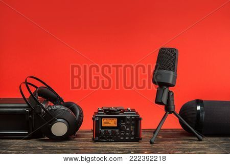 equipment for field audio recording on red background.  usb microphone, recorder, headphones, portable case and windshield