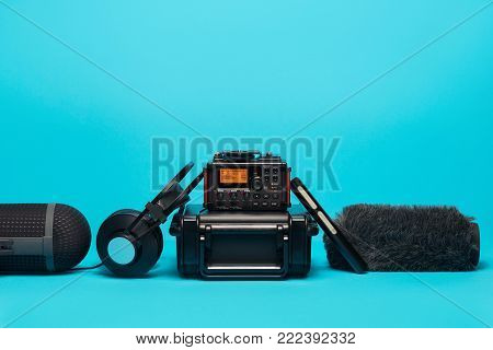 equipment for field audio recording on blue background. shotgun microphone, recorder,  windshield, headphones and case.