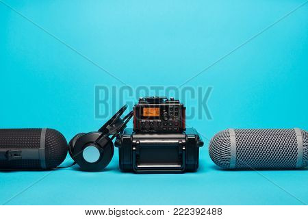 equipment for field audio recording on blue background. Windshield, recorder, portable case and headphones