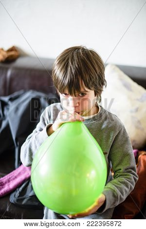 Child Inflates Green Balloon For Birthday Party In His Home