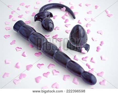 Three black rubber sex toys (dildo, butt plug and tail) are on a white background. Around are scattered little pink hearts. Image on the topic of advertising a sex shop or a variety of sexual life