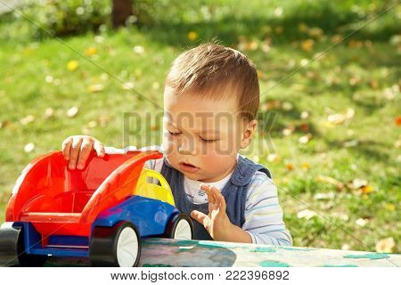little boy playing with a toy truck. child plays with a toy car outdoors