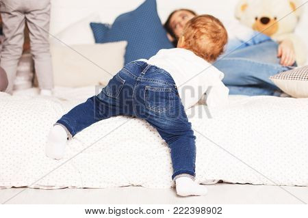 The Child Crawls Out Of Bed. Child Near The Bed