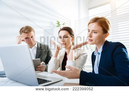 Obligatory looses. Worried upset three colleagues gazing at the screen while sitting and laptop standing on the table
